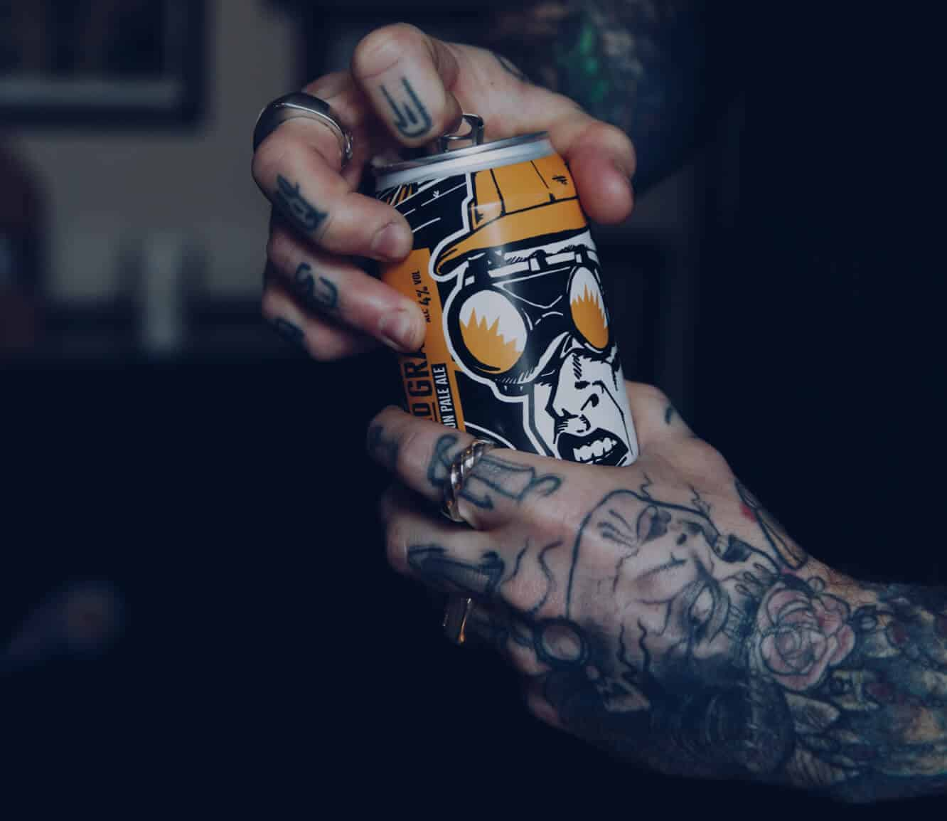 Tattooed hands opening a can of Hard Graft session pale ale